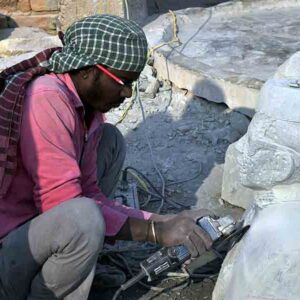 Local carver sculpting a bust without any protection equipment. The Stone dust affects carvers and their family members.